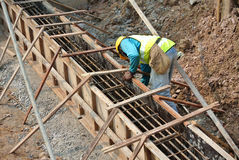 Group of construction workers fabricating ground beam formwork Royalty Free Stock Image