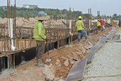 Group of construction workers installing ground beam formwork Royalty Free Stock Photos