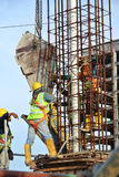 A group of construction workers pouring concrete into column form work Royalty Free Stock Image