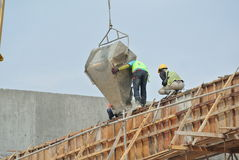 A group of construction workers pouring concrete into formwork Stock Photo