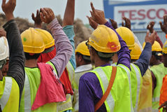 Group of construction workers raise their hand and assemble at the open space Royalty Free Stock Photo