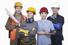 Group of construction workers standing against white background, smiling, portrait Stock Images