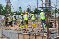 Group of construction workers standing at the construction site. Royalty Free Stock Photo