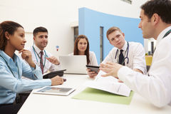Group Of Consultants Sitting At Table In Hospital Meeting Royalty Free Stock Photos