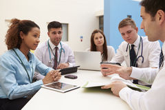 Group Of Consultants Sitting At Table In Hospital Meeting Royalty Free Stock Images