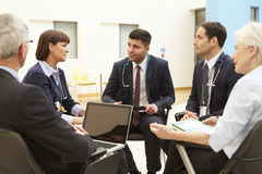 Group Of Consultants Sitting At Table In Hospital Meeting Stock Photo