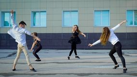 Group of contemporary dancers freestyling outside in summertime.