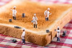 Group of cooks or chefs on a slice of white toast. Group of miniature cooks or chefs on a slice of white toast in a concept of teamwork in preparing food and stock photography