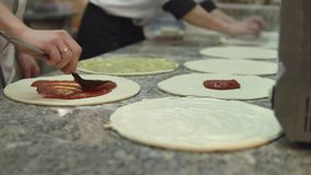 A group of cooks evenly put the sauce on the circles of the dough for making pizza stock video