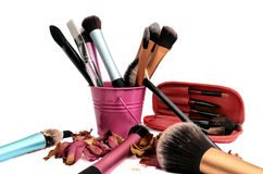 Group of cosmetic brushes on white background. A consistent group of cosmetic brushes (with cheek powder spread in three shades) and roses petals spread around a stock photography