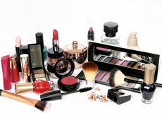 Group of cosmetics on white background. A consistent group of cosmetics in different colors, sizes and shapes (cream, perfume, eyes multi-shades with mirror lids royalty free stock photography