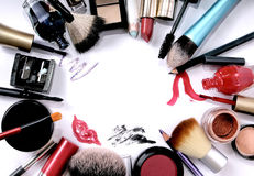 Group of cosmetics on white background. A consistent group of cosmetics in different colors, sizes and shapes (with zig-zag shades of lipstick, eyeliner and nail stock image