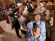 Group of Cowboys Point Guns in Bar. Armed senior women and crowd points guns in old saloon Royalty Free Stock Photo