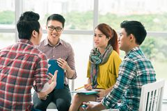 Group of coworkers. Group of Asian coworkers having briefing in the office royalty free stock image