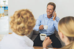 Group of coworkers having coffee break. Enjoying little coffee on my break. Cropped shot of businessman sitting in meeting with his coworkers, drinking coffee Stock Photography