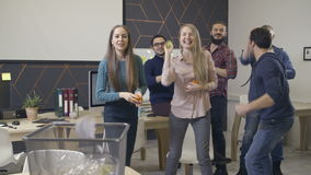 Group of coworkers throws paper into wastebasket