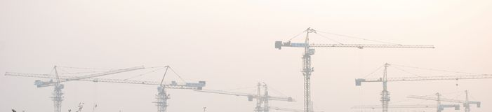 Group of cranes. Evening, constriction of the house Royalty Free Stock Photo