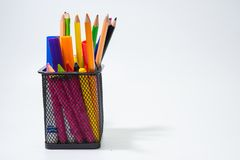 Crayons and color pencils all put in the black bucket box isolate on white background. Group of crayons and color pencils all put in the black bucket box Royalty Free Stock Photo