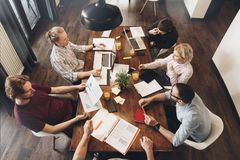 Group of creative coworkers sit around a wooden table in an open royalty free stock photography