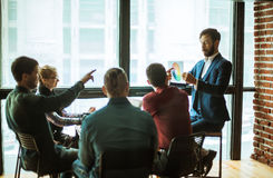 Group of creative designers discuss the color palette in a moder. Group of designers discussing a new color palette in the workplace in a modern office royalty free stock images