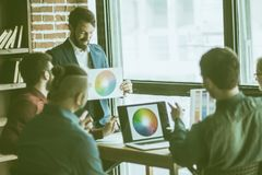 Group of creative designers discuss the color palette in a moder. Group of designers discussing a new color palette in the workplace in a modern office stock image