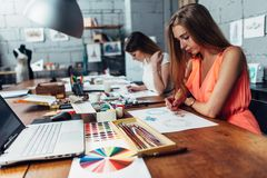Group of creative fashion designers drawing sketches of accessories working in studio.  Royalty Free Stock Photography