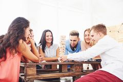 Group of creative friends sitting at wooden table. People having fun while playing board game Royalty Free Stock Image