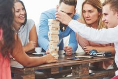 Group of creative friends sitting at wooden table. People having fun while playing board game.  stock photo