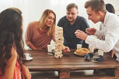 Group of creative friends sitting at wooden table. People having fun while playing board game.  royalty free stock images