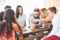 Group of creative friends sitting at wooden table. People having fun while playing board game stock images