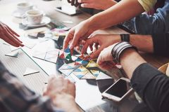 Group of creative friends sitting at wooden table. People having fun while playing board game.  stock photography