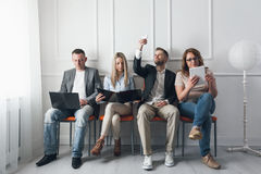 Group of creative people sitting on chairs in waiting room Stock Image