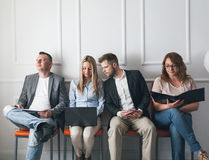 Group of creative people sitting on chairs in waiting room Royalty Free Stock Image