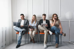 Group of creative people sitting on chairs in waiting room. Group of young creative people sitting on chairs in waiting room Stock Photos