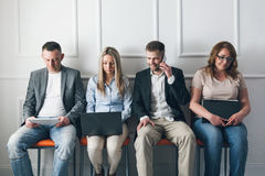 Group of creative people sitting on chairs in waiting room Royalty Free Stock Images