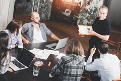Group of creative project managers analyzes development of startup. Business people work for papers and laptop in loft space. Presentation of creative project Stock Photo