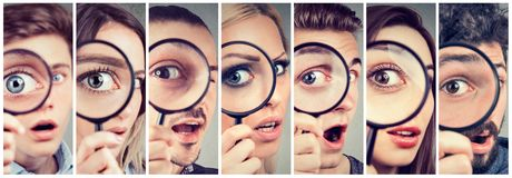 Group of curious women and men looking through a magnifying glass. Group of curious young women and men looking through a magnifying glass royalty free stock photos