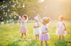 Group of cute children blowing soap bubbles Royalty Free Stock Image
