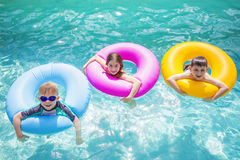 Group of cute kids playing on inflatable tubes in a swimming pool on a sunny day. Bright colorful fun summer photo with copy space stock image