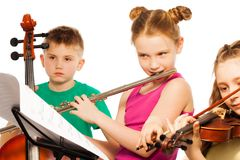 Group of cute kids playing on musical instruments. Together on white background Stock Photos