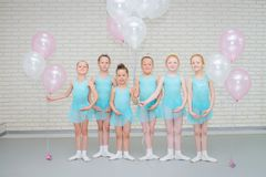 Happy cute little ballet dancers with air ballons smiling at looking at camera at dance school class. stock photos
