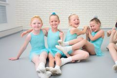 Group of cute little ballet dancers having fun at dance school class. stock photo