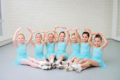 Group of cute little ballet dancers looking at camera at dance school class. royalty free stock photo