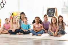 Group of cute little children sitting on floor. Kindergarten playtime activities stock photography