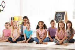 Group of cute little children sitting on floor. Kindergarten playtime activities stock image