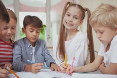Group of cute little kids drawing together in art class stock photo