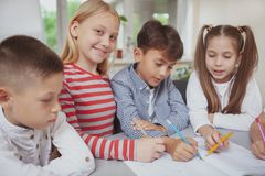 Group of cute little kids drawing together in art class stock photos