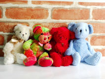 A group of cute teddy bears sitting together against with wallpaper Stock Photo