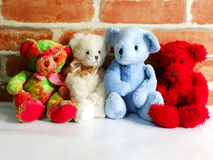 A group of cute teddy bears sitting together against with wallpaper Stock Images