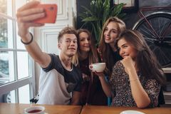 Group of cute teenagers taking selfie with cellphone while sitting in a restaurant with interior in retro style Stock Photos